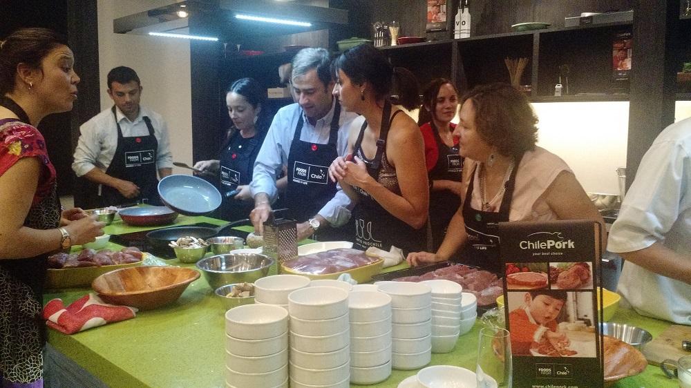 Periodistas y autoridades reunidas en torno a la preparación de solomillo de cerdo al horno y risotto de mote. Todos esforzándose por obtener el primer lugar.